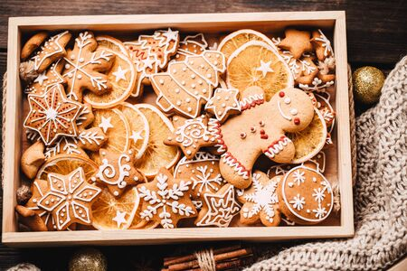 Christmas and New Year traditions concept. Gingerbread cookies, decorations, gift boxes and knitted blanket