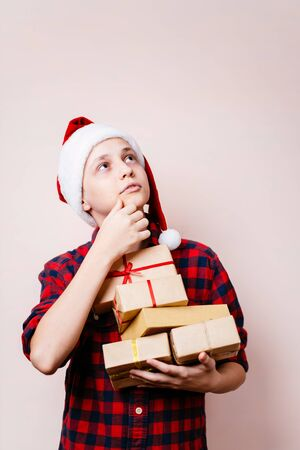 Pensive boy in Santa hat with stack of gift boxes
