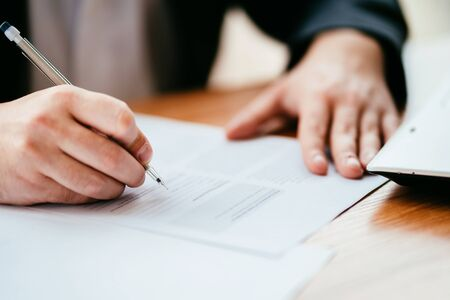 Businessman filling document, signing contract