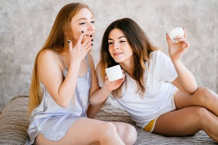 Female friends testing and applying face cream