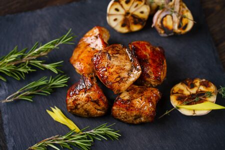 Grilled pork meat served on slate Stock Photo