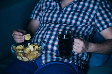 overweight man watching tv with junk food and beer