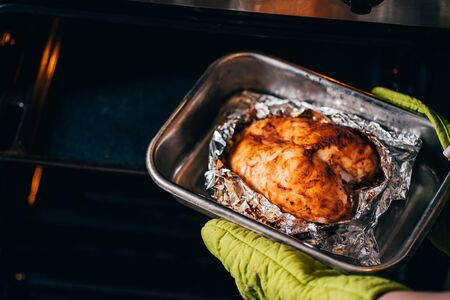 Woman taking baked chicken breasts from oven
