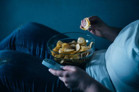 overweight woman with tv remote and junk food Stock Photo