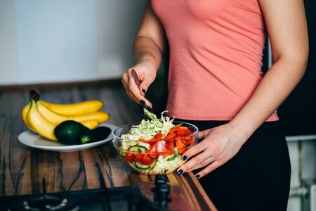 Fit woman cooking vegetable salad at her kitchen