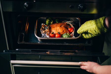 Cooking healthy food. Woman taking baked chicken breasts from oven. Fat- free, no fry meals