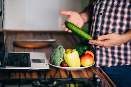 Overweight man recording video cooking healthy food at home kitchen. Cooking recipe online culinary blog, weight loss support Stock Photo