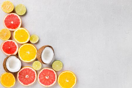 Summer holidays, resort vacation, exotic fruits background. Summertime vibes. Composition with citrus slices on stone grey surface, copy space