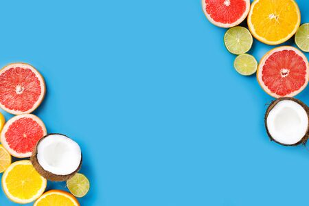 Summer holidays, resort vacation, exotic fruits background. Summertime vibes. Composition with citrus slices on blue surface, copy space Banco de Imagens