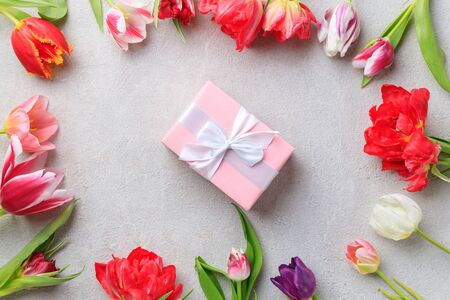 Spring floral design greeting card. Multicolored tulips border and gift box on grey stone surface. Copy space Imagens