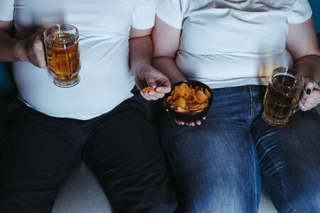 Overweight couple watching tv eating junk food