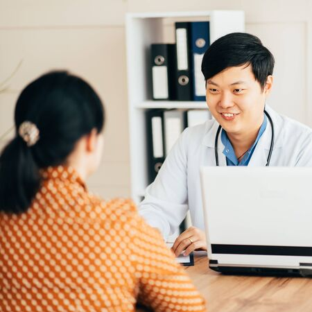 Asian doctor and female patient talking in clinic