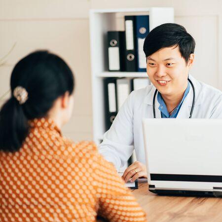 Asiatische Ärztin und Patientin, die in der Klinik sprechen