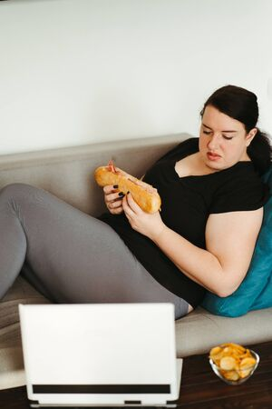Woman eating unhealthy food watching series online