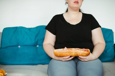 Obese woman sitting on sofa eating unhealthy food