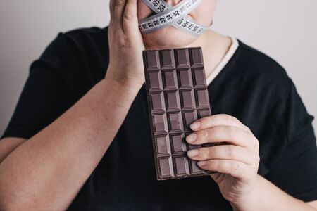 Woman with chocolate, eating disorder struggle