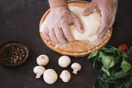 Chef baker hands kneading pizza dough, close up