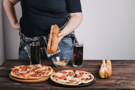 Overweight woman with big amount of junk food