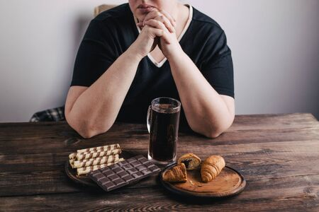 Overweight woman with big amount of sugary food 免版税图像