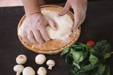 Chef baker hands kneading pizza dough at kitchen. Food delivery, restaurant meals preparing concept