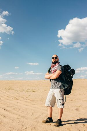 Tourist with backpack traveling through desert