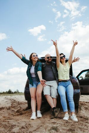 Friends traveling by car enjoy vacation together Фото со стока