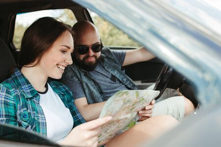 Young joyful couple using map traveling by car