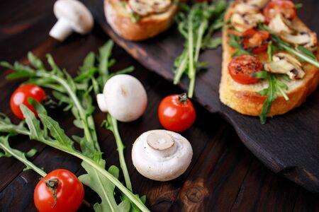 Tomato and mushroom bruschettas with arugula Foto de archivo
