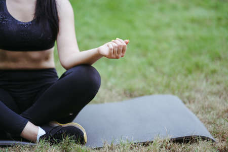 Outdoor yoga. Unrecognizable young woman relaxing in nature park meditating on fitness mat. Copy space. Leisure, self development, mental health and contemplation