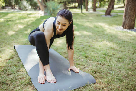 Young sporty woman doing morning yoga in the park. Healthy lifestyle, sport, leisure activity concept, mental health and contemplation Foto de archivo