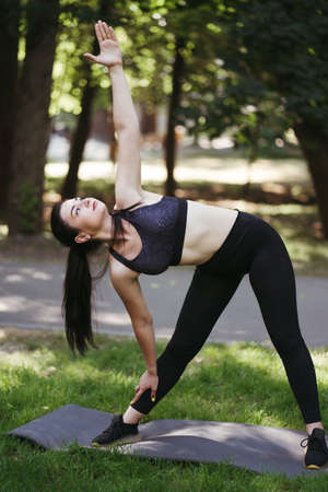 Outdoor training. Fit woman doing stretching exercises on fitness mat warming up muscles in city park. Balance, healthy lifestyle, self development Foto de archivo
