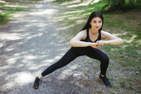 Fit woman runner doing stretching exercise, preparing for morning workout in the park. Street fitness, sport, exercising, people and healthy lifestyle concept. Foto de archivo