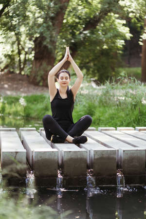 Outdoor yoga. Young woman meditating in the park near running water. Nature, open air leisure activity. Self development, mental health and contemplation concept