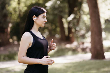 Enjoy music, clear sound, freedom, technology. Sporty woman listening to favorite soundtrack in wireless earphones during outdoor workout