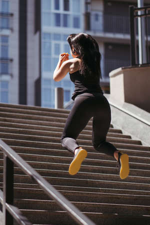 Street fitness, cardio workout, sport in the city. Young fit woman exercising on the stairs. Endurance and healthy lifestyle