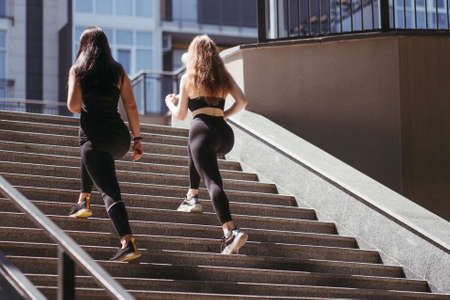 Street fitness, cardio workout, sport in the city. Two sporty women exercising together running outdoors. Endurance, healthy lifestyle and motivation
