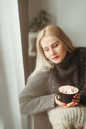 Cozy winter weekend, home scene, hygge concept. Warming hygge mood. Woman enjoy hot chocolate with marshmallows Foto de archivo