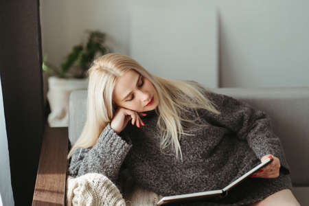 Cozy atmosphere, winter holidays at home. Woman enjoy reading a book sitting at coach in cuddly modern room. Cozy atmosphere, winter holidays
