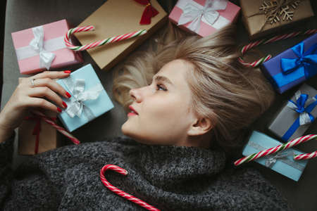 Sale and shopping. Christmas, New Year, winter holidays festivity and celebration concept. Cute young woman with many present boxes. Family, love, surprise and joy