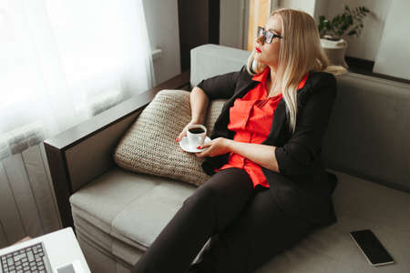 Woman working on laptop at home, enjoying coffee