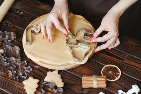 Christmas and New Year holidays, family weekend activities, celebration traditions. Woman cutting cookies of raw gingerbread dough