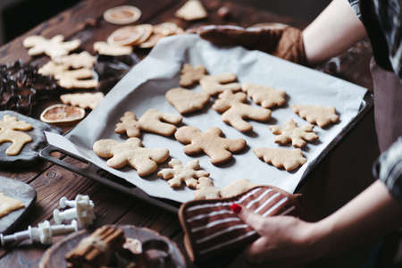 Christmas bakery. Festive food, cooking process, family culinary, Christmas and New Year traditions concept. Woman hands holding homemade gingerbread cookies Foto de archivo