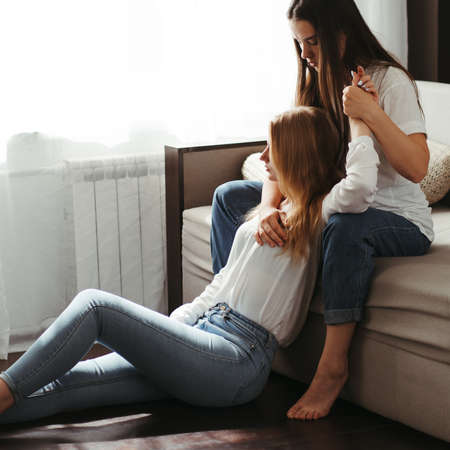 Human relationships, lgbt family, friendship. Two young women in living room
