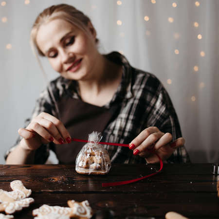 Christmas, New Year, DIY, holidays preparation and creativity concept. Woman packing Christmas gingerbread cookies.
