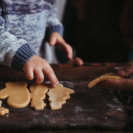 Christmas and New Year holidays, family time, weekend activities, celebration traditions. Mother, father and son making festive homemade gingerbread cookies Foto de archivo - 155197989