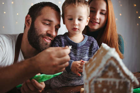 Christmas, family time, holiday preparations. Mother, father and son decorating Christmas gingerbread house