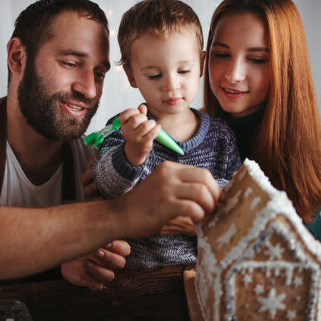 Christmas and New Year celebration traditions. Family time, holiday preparations. Mother, father and son decorating Christmas gingerbread house Foto de archivo