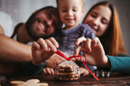 Christmas, family time, holiday surprise. Mother, father and son packing Christmas gingerbread cookies. Christmas and New Year traditions concept