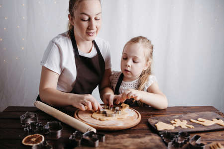 Christmas and New Year traditions concept. Festive food, cooking process, family culinary. Mother and daughter baking gingerbread cookies together