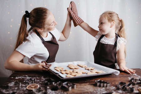 Mother and daughter giving high five holding pastry board with freshly baked gingerbread cookies. Festive food, cooking process, family culinary, Christmas and New Year traditions concept